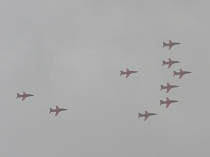 Nine Red Arrows almost invisible in rain clouds