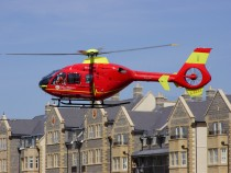 Red and Yellow Eurocopter EC135T, G-BZRS, at rooftop level on the Sea-front
